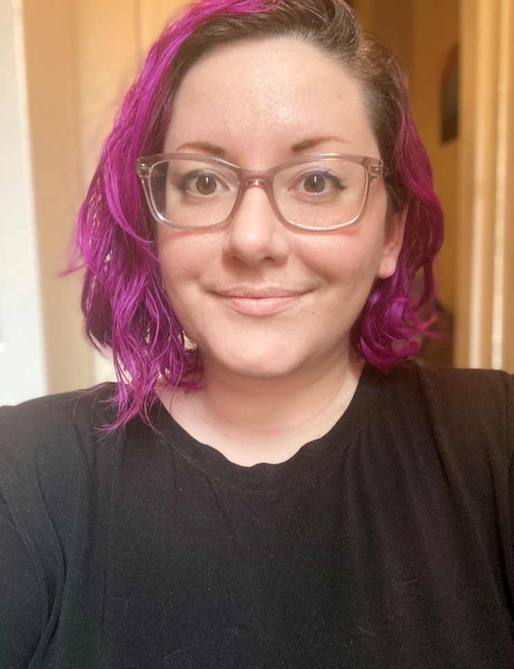 Portrait-style photograph of Chel, smiling and looking directly at the camera. Chel has fair skin and shoulder-length wavy purple hair. They are wearing clear plastic framed glasses, subtle winged eyeliner, and a black shirt.